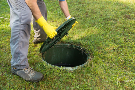 Opening septic tank lid. Cleaning and unblocking septic system and draining pipes.