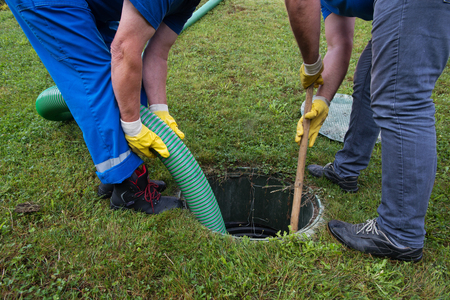 Emptying household septic tank. Cleaning and unblocking clogged drain with vacuum pipe and spear. Stock Photo