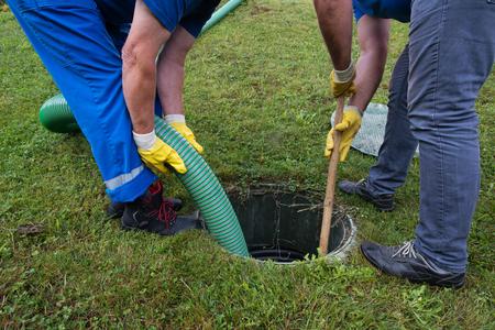 Vidage de la fosse septique domestique. Nettoyage et déblocage d'un drain obstrué avec un tuyau d'aspiration et une lance. Banque d'images