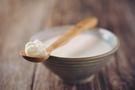 Kefir Grains on Wooden Spoon with a Cup of Kefir in background. Homemade Organic Probiotic. Shallow Depth of Field.