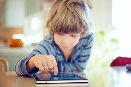 Little boy using digital tablet. Selective focus on child's finger, shalow depth of field.