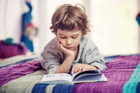 Cute little boy lying on bed reading book 스톡 콘텐츠