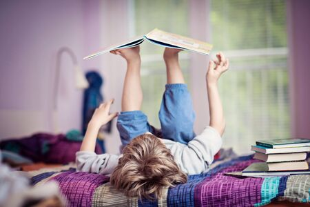 Little boy lying on bed playing with books. 스톡 콘텐츠 - 133965984