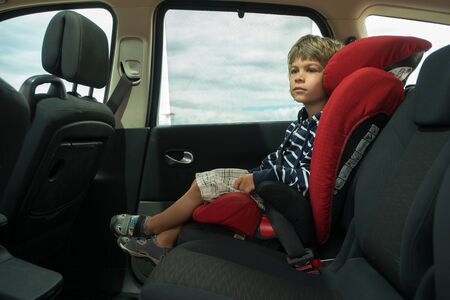 Little boy sitting in high back booster car seat fasten with seat belt. Child safety.