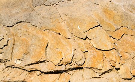 a strongly cracked yellow background of stone  photo