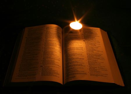 A bible open on a table next to a candle Stock Photo - 5559105
