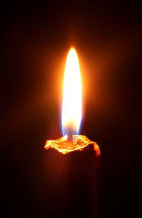 holy night: burning candle on a black background