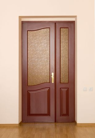 closed brown entrance door in a wall