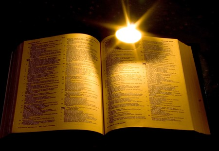 A bible open on a table next to a candle photo