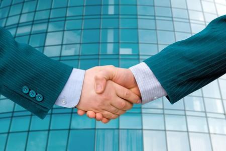 businessmen handshake: Handshake with modern skyscrapers as background