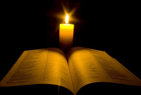 bible christmas: A bible open on a table next to a candle