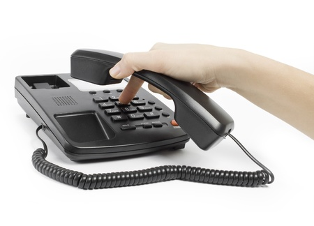 dialing: office black telephone with hand isolated on white Stock Photo