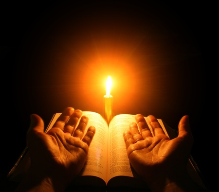 A bible open on a table next to a candle Stock Photo - 9458220