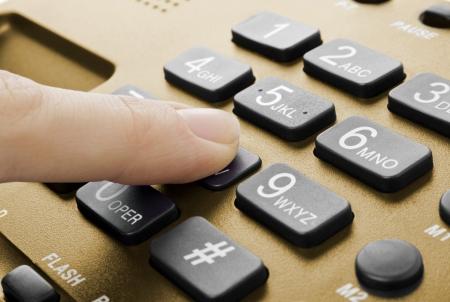 wijzerplaat: kantoor zwarte telefoon met hand op wit wordt geïsoleerd