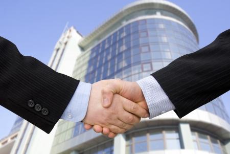 saludo de manos: Apret�n de manos con modernos rascacielos como fondo
