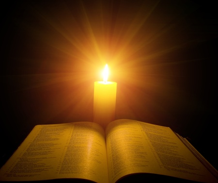 candle: A bible open on a table next to a candle