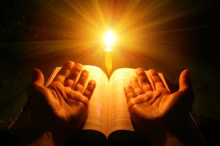 biblia: Una Biblia abierta sobre una mesa junto a una vela