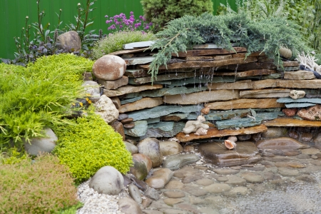 home garden: decorative pool of stone, water and plant Stock Photo