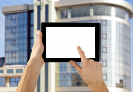 tablet computer isolated in a hand on the skyscraper backgrounds photo
