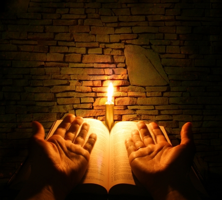 jesus hands: A bible open on a table next to a candle