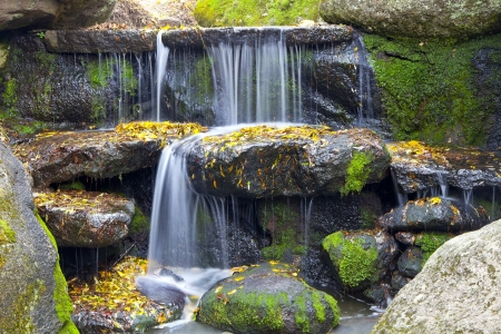 river stones: waterfall in the forest. beautiful background of stone, water, moss.
