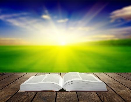 夕日の光線で木の板に開かれた本。概念の教育の背景