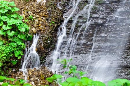 murmur: waterfall in the mountain forest. beautiful background of stone, water, moss. Stock Photo