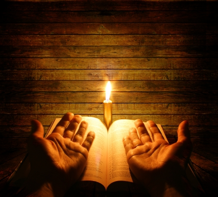 hand of god: A bible open on a table next to a candle