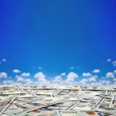 money pile: big pile of money. stack of american dollars on the sky backgrounds  Stock Photo