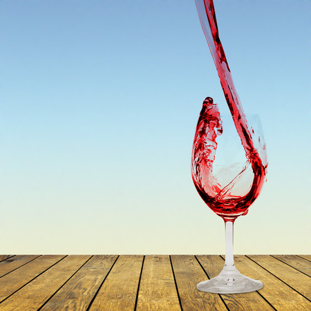 red wine being poured into a glass on a white background Stock Photo