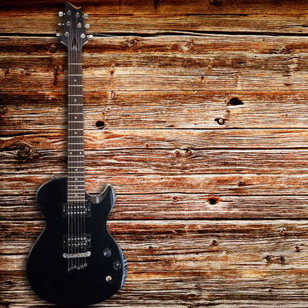 Black electric guitar on wood background