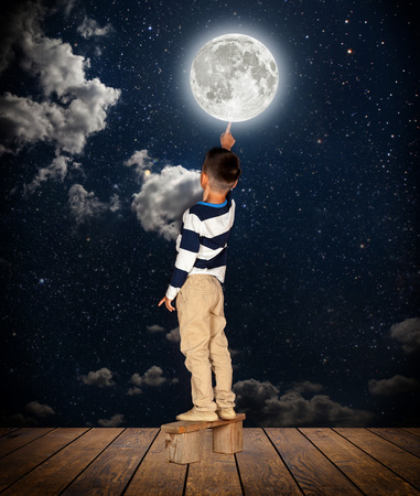 boy pulls out his finger to the moon Stock fotó - 113561878