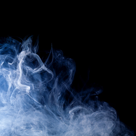blue smoke: blue smoke swirls over black background Stock Photo