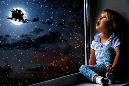the child looks out the window on Christmas day Archivio Fotografico