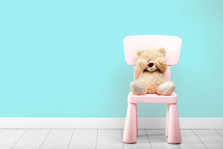 little bear sits in a turquoise room on a chair with his eyes closed hands 版權商用圖片