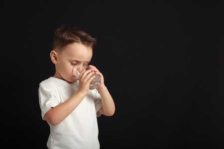 a child drinks water on a black background