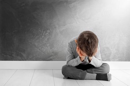 bambino la cui depressione è seduto sul pavimento