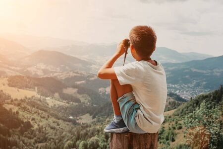 Boy standing on of stump in summer mountains at sunset and enjoying view of nature