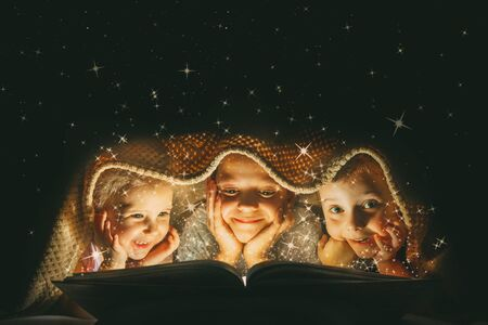 childrens reading a book under a blanket with light