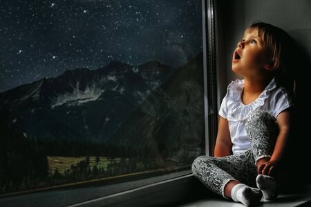 the child looks out the window into the night sky Standard-Bild - 132821606
