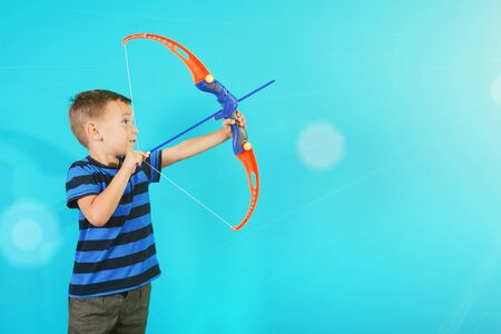Boy shoots a bow at a target on the blue backgrounds