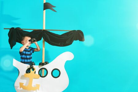 Little child boy playing with cardboard ship on blue wall background