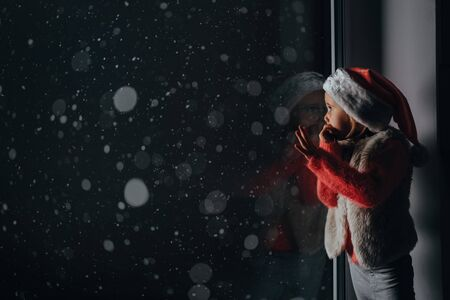 the child looks out the window on christmas of Jesus Christ. Stock Photo