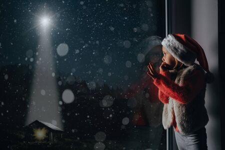 het kind kijkt uit het raam met kerst