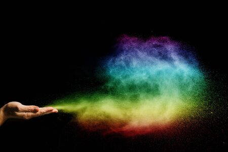 Color dust particle swell with hands on black background.