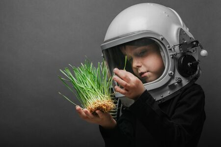 A small child holds plants in an airplane helmet. the child looks at the grass through the glass. The concept of environmental protection. Stock fotó