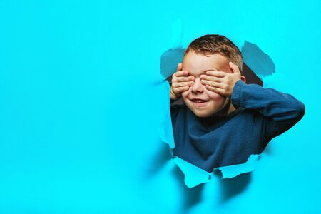 Happy cute boy is having fun played on black background wall. climbs through a hole in the paper. Bright photo of a boy. Banco de Imagens