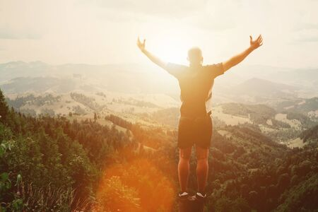 Hombre de pie sobre el tocón en las montañas de verano al atardecer y disfrutando de la vista de la naturaleza