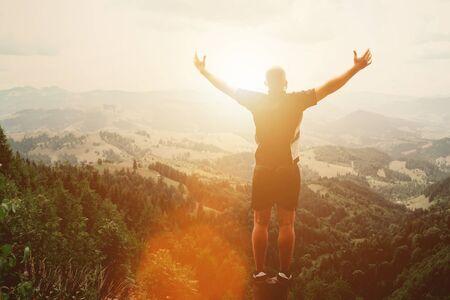 Uomo in piedi su un ceppo in montagna d'estate al tramonto e godersi la vista della natura