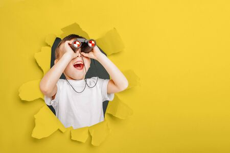 Happy cute boy is having looking through binoculars through a torn hole in yellow paper